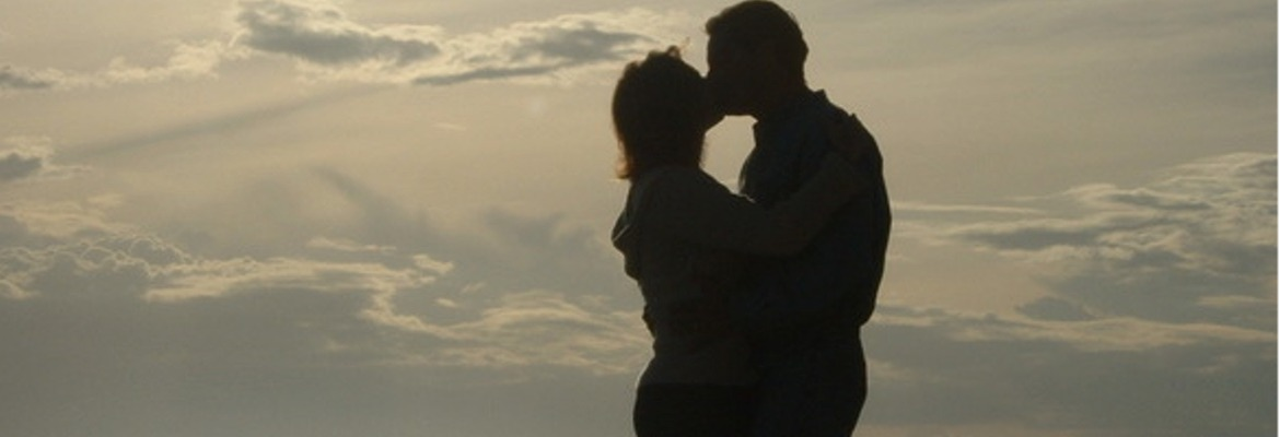 man and lady kissing in front of a sunset
