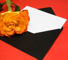 Yellow rose on top of card half in envelope
